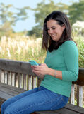 Pretty Woman and Techonology. Pretty brunette woman wearing a green shirt and blue jeans enjoying using her wireless device while sitting on a park bench royalty free stock photography