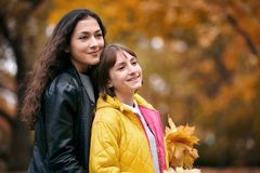 Pretty woman and teen girl are posing with bunch of maple`s leaves in autumn park. Beautiful landscape at fall season royalty free stock photos