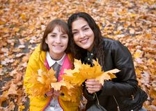 Pretty woman and teen girl are posing with bunch of maple`s leaves in autumn park. Beautiful landscape at fall season royalty free stock image