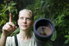 Pretty Woman with Telescope in the Rain Forest Royalty Free Stock Image