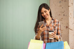 Pretty woman texting while doing some shopping Royalty Free Stock Images