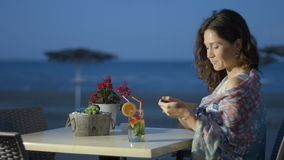 Pretty woman texting on mobile phone with smile on face, rest at seaside cafe. Stock footage stock footage