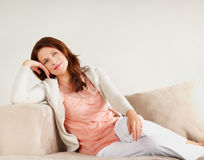 Pretty woman thinking while on couch Royalty Free Stock Photos