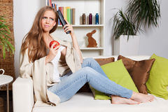 Pretty woman thinking about watching TV. In the livingroom Royalty Free Stock Photography