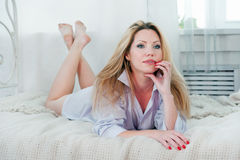 Pretty woman thinks while lying on the bed Stock Images