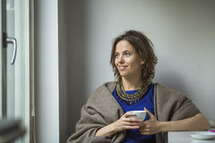 Pretty  woman thoughtfully with a Cup of tea near the window. Royalty Free Stock Photography