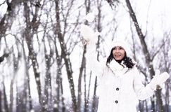 Pretty woman throwing snowball Royalty Free Stock Photos