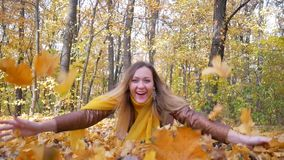 Pretty Woman Throws Up Yellow Leaves and Smiles in Forest or Park. On background of trees with yellow foliage in autumn. Female in orange scarf and brown stock video footage