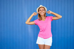 Pretty woman. To loud! Young pretty woman  closes her ears with fingers refusing to listen to something. Blue background Royalty Free Stock Photo