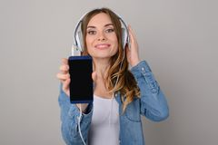 Pretty woman with toothy smile listening to music via headphones stock image