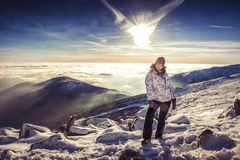 Pretty woman on top of mountain, female hiker admiring winter scenery on a mountaintop alone Stock Images