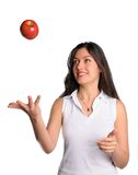 Pretty woman tosses apple in air isolated. Pretty brunette woman on isolated background tosses apple in air Stock Images