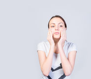 Pretty Woman Touching her Cheeks with Both Hands Stock Photo