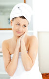 Pretty woman with towel putting cream on her face Stock Photos