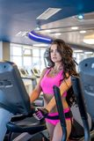 Pretty woman training on simulator in fitness room Stock Photos