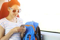Pretty woman traveling by train sitting near the window using sm Stock Photo