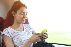 Pretty woman traveling by train sitting near the window using sm Stock Images