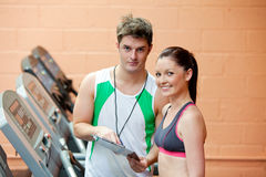 Pretty woman on a treadmill with her coach Stock Photography
