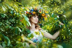 Pretty woman among tree leaves. Stock Photos