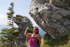 Pretty woman trekker drinking under big rock with signpost Royalty Free Stock Images