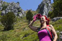 Pretty woman trekker wiping sweat from her forehead Stock Images