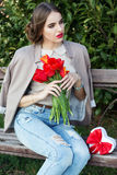 Pretty woman with tulips sitting on the bench Royalty Free Stock Photos