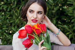 Pretty woman with tulips sitting on the bench Stock Photography