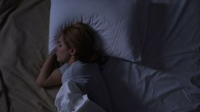 Pretty woman turning in her bed feeling discomfort, bad quality of mattress
