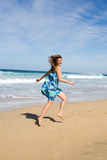 Pretty woman in turquoise dress on the beach Stock Photo