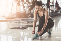 Pretty woman tying shoelaces in a gym Stock Photo