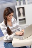 Pretty woman typing on laptop at home Royalty Free Stock Image