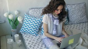 Pretty woman typing text on a laptop sitting on a bed in a cozy room. stock footage