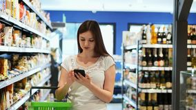 Pretty woman use phone with shopping basket in supermarket, texting sms