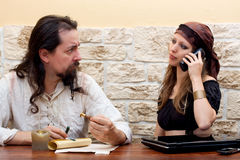 Pretty woman uses technology, man is skeptical Royalty Free Stock Image