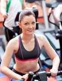 Pretty woman using a bicycle in a gym Royalty Free Stock Images