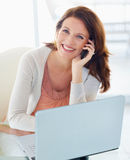 Pretty woman using cellphone with laptop in front Royalty Free Stock Photo