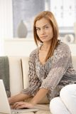 Pretty woman using computer on sofa Stock Image
