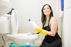 Pretty woman using disinfectant and brush to clean toilet. Cute waitress cleaning hotel bathroom toilet seat with disinfectant and brush Stock Photo