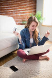 Pretty woman using her credit card to buy online. Sitting on the floor in the living room Stock Images
