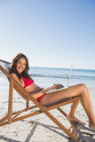 Pretty woman using her laptop while relaxing on her deck chair. Pretty woman on the beach using her laptop while relaxing on her deck chair Royalty Free Stock Photo