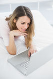 Pretty woman using her notebook lying on her bed. In bright bedroom stock photography