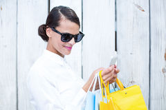 Pretty woman using her smartphone holding shopping bags Royalty Free Stock Image