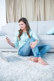 Pretty woman using her smartphone and laptop. At home in the living room Royalty Free Stock Photography
