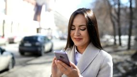 Woman using her smartphone outdoors. Pretty woman using her smartphone outdoors stock footage