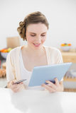 Pretty woman using her tablet for home-shopping while sitting in her kitchen Royalty Free Stock Photography