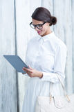 Pretty woman using her tablet pc. In front of wooden grey planks Royalty Free Stock Image
