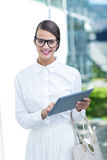 Pretty woman using her tablet pc looking at camera. Outside Stock Image
