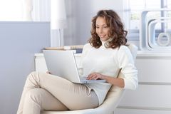 Pretty woman using laptop computer at home Stock Photography