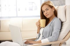 Pretty woman using laptop having tea Stock Photos