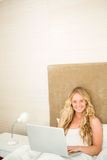 Pretty woman using laptop in her bed Royalty Free Stock Photos